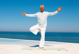Full length image of a mature man practicing yoga at the sea sho
